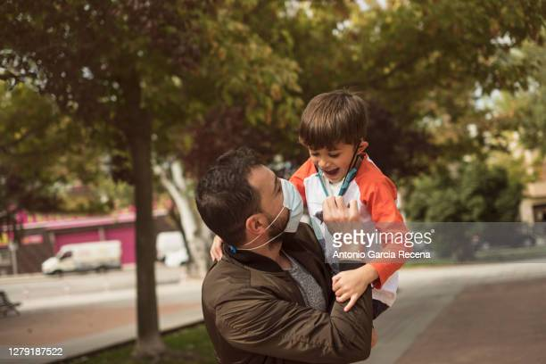 father plays with his children in the park during the covid-19 pandemic, removing mask. - removing stock pictures, royalty-free photos & images