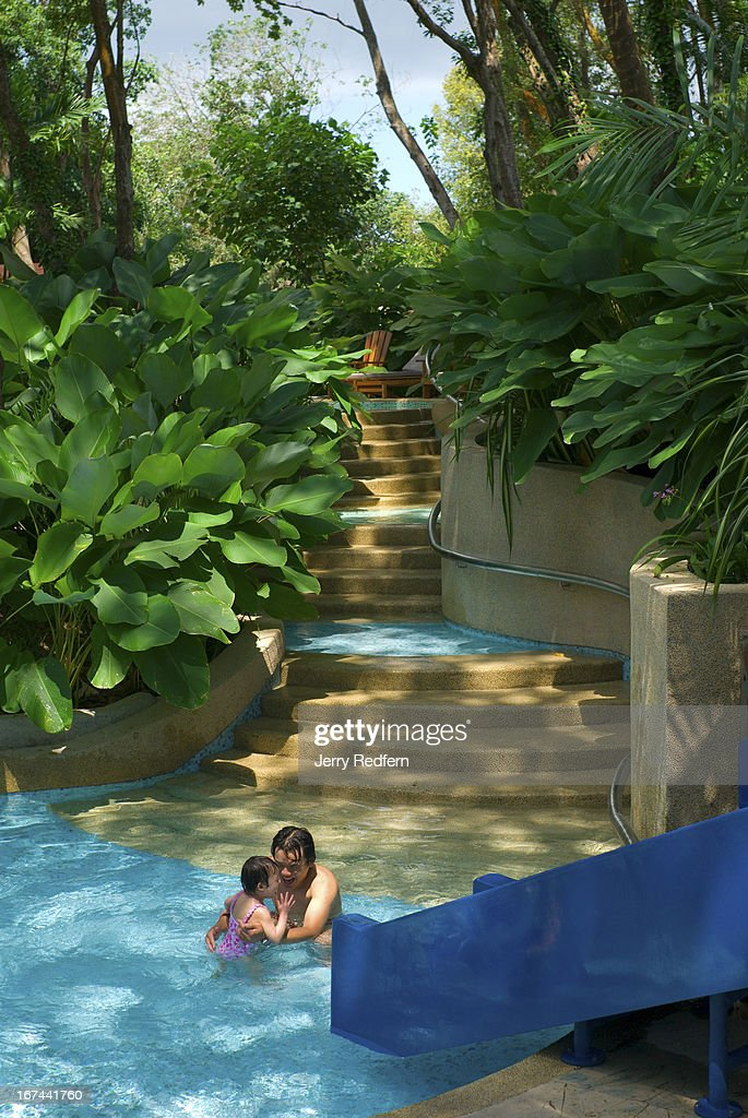 A father plays with his daughter in the children's pool at the Amara Sanctuary Resort on Sentosa Island. The new luxury hotel incorporates an old British army barracks into its modern design..