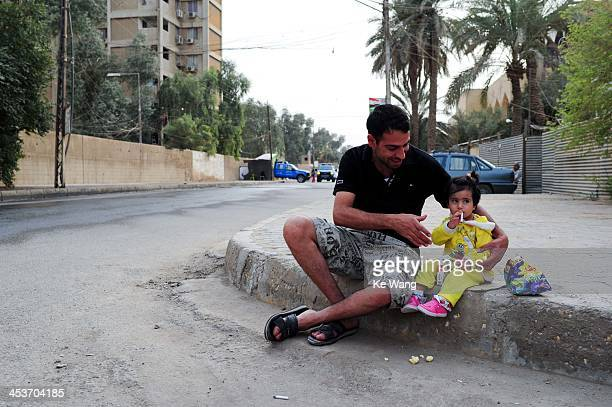 Father plays with his daughter on the street of Baghdad of Iraq on March 26, 2012.