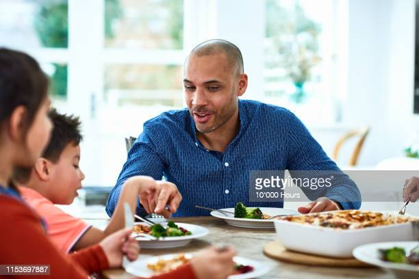 father pointing at fresh vegetables on son's plate - filipino family dinner stock pictures, royalty-free photos & images