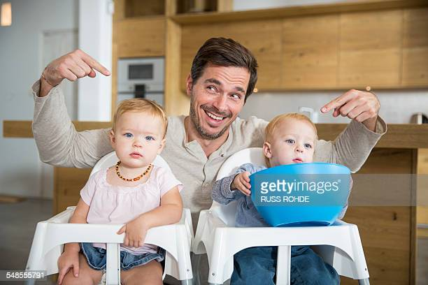 Father pointing at male and female twin toddlers in high chairs