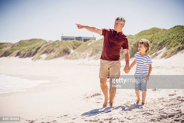 Father pointing while walking with son on shore