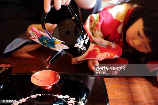 father pouring new year's spiced sake called otoso with daughter - dia de ano novo imagens e fotografias de stock