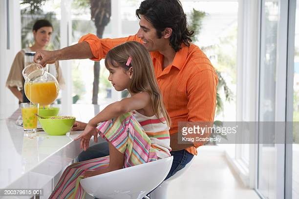 Father pouring orange juice for daughter (7-9) sitting in kitchen