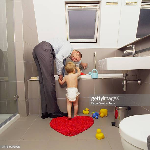 father preparing bath for baby - man bending over from behind stock photos and pictures