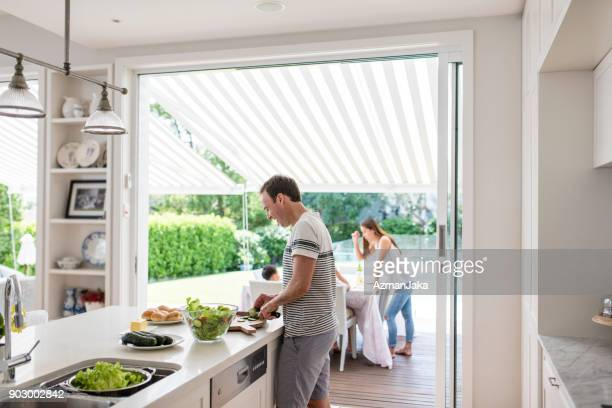 father preparing food for barbecue - domestic life stock pictures, royalty-free photos & images