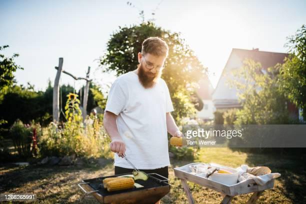 father preparing food on bbq for family - grill zubereitung stock-fotos und bilder