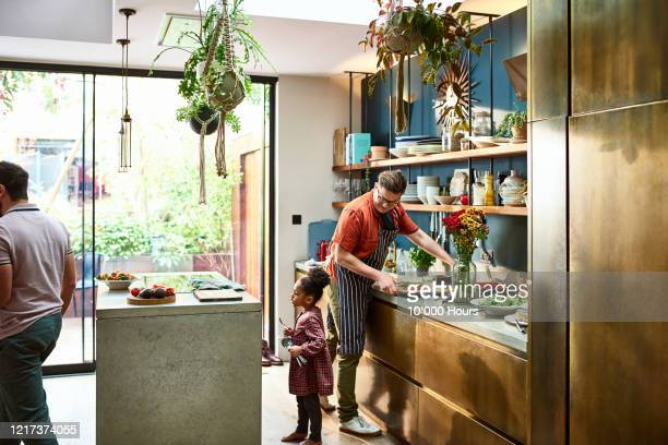 father preparing meal with young girl in stylish kitchen - primary school child stock pictures, royalty-free photos & images