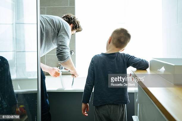 father preparing the bathtub for his son - darse un baño fotografías e imágenes de stock