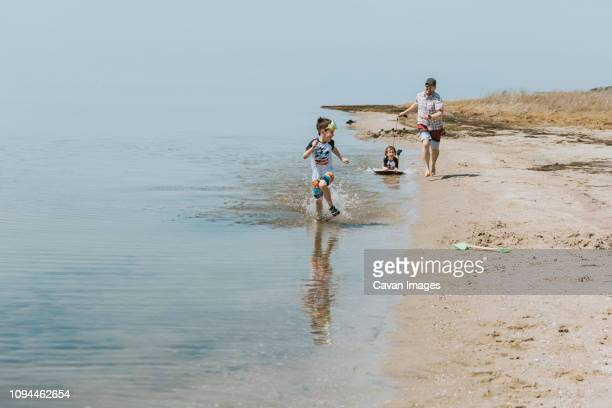 father pulling boy sitting on surfboard while running behind son in sea during sunny day - outer banks stock pictures, royalty-free photos & images