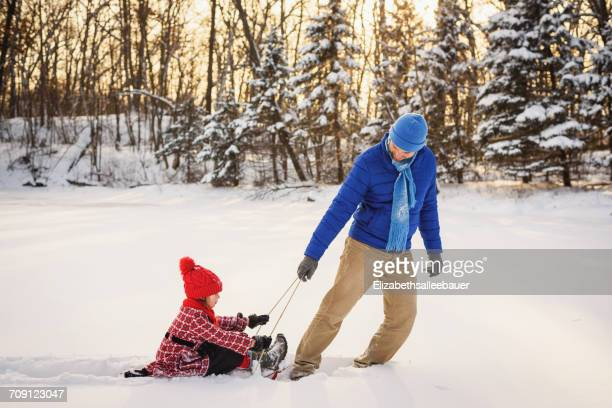father pulling daughter on a sled in the snow - tobogganing stock pictures, royalty-free photos & images