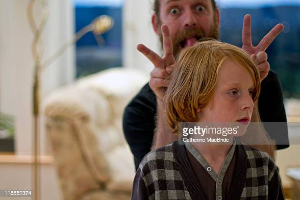 father pulling faces behind his sons head - catherine macbride stock pictures, royalty-free photos & images