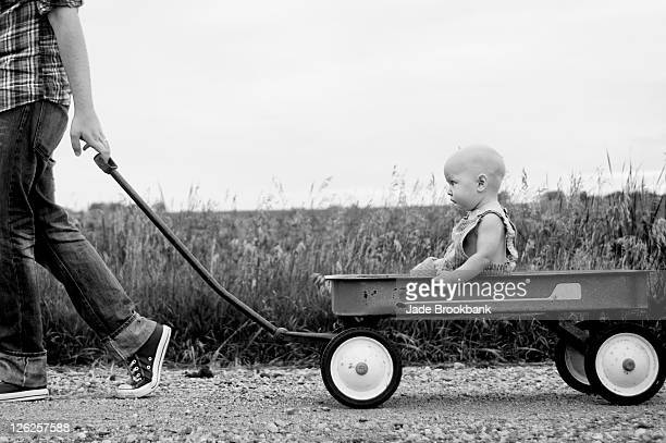 father pulling son in wagon - toy wagon stock photos and pictures