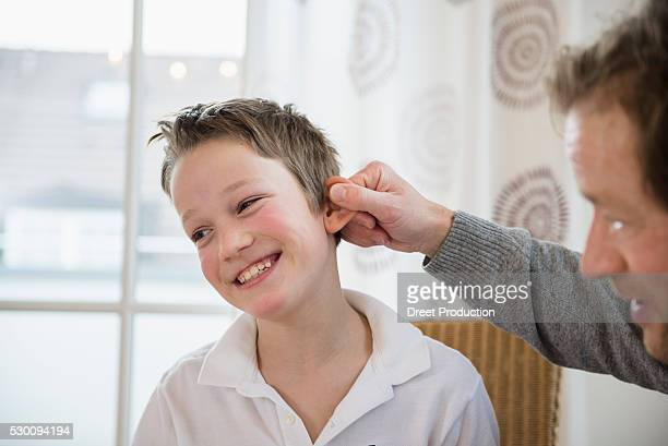 Father pulling son's ear