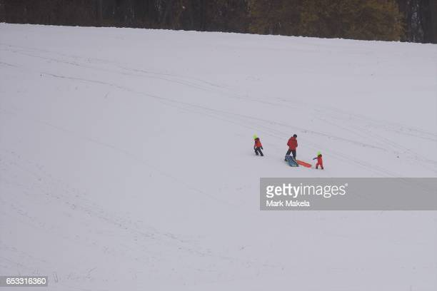 A father pulls his children walk up a hill for sledding at Valley Forge National Historical Park March 14 2017 in Valley Forge Pennsylvania A...
