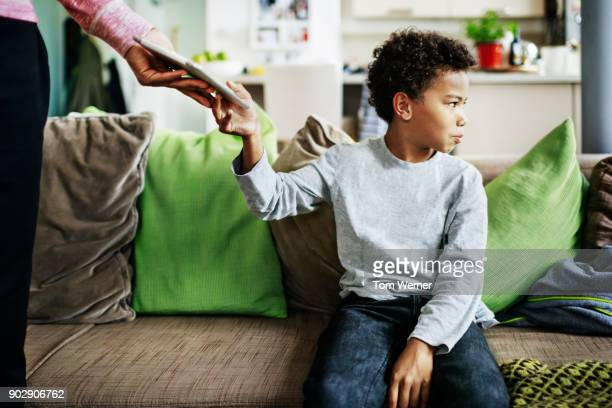 father punishes son by taking tablet off him - penalty stock pictures, royalty-free photos & images