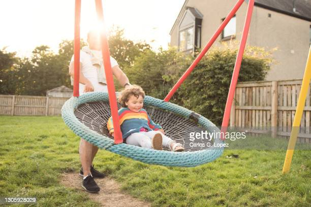 a father pushes her daughter as she rides a big swing in a sunny day in a public play park - season 3 stock pictures, royalty-free photos & images
