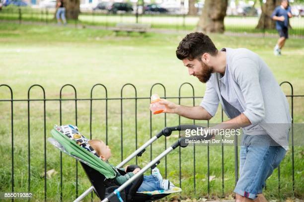 Father pushing baby pram while showing baby bottle to his son.