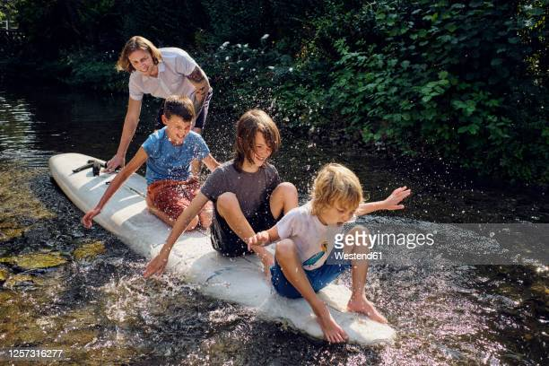 father pushing boys splashing water while sitting on paddleboard in stream - weekend activities stock pictures, royalty-free photos & images