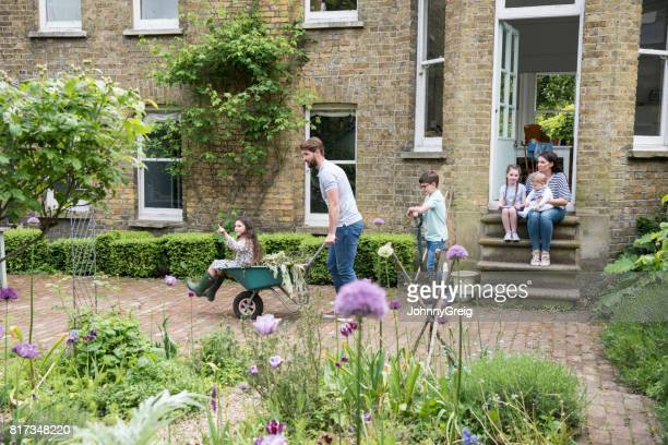 Father pushing daughter in wheelbarrow in back garden, family watching