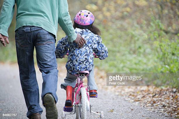 Father pushing daughter on bike
