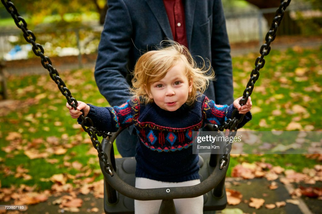 Father pushing daughter on playground swing : Stock Photo