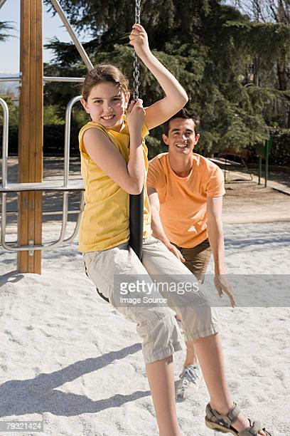Father pushing daughter on swing
