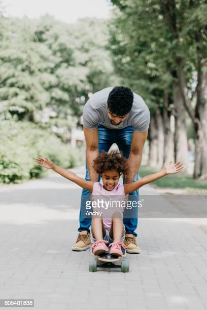 Father pushing his daughter on the longboard