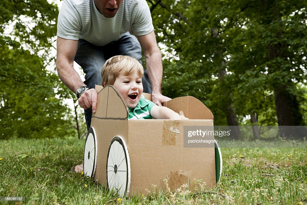 Father pushing his son in a cardboard box on grass : Stock Photo