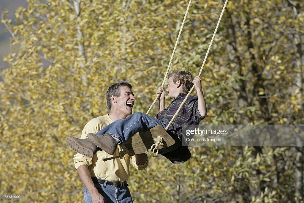 Father pushing his son on a swing : Stockfoto