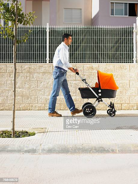 Father pushing pram on pavement, Alicante, Spain,
