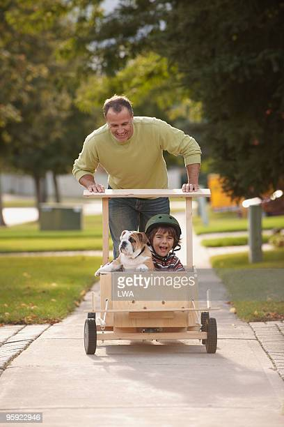 Father Pushing Son and Puppy In Soap Box Car