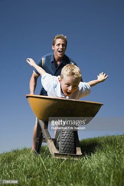 Father pushing son in a wheelbarrow