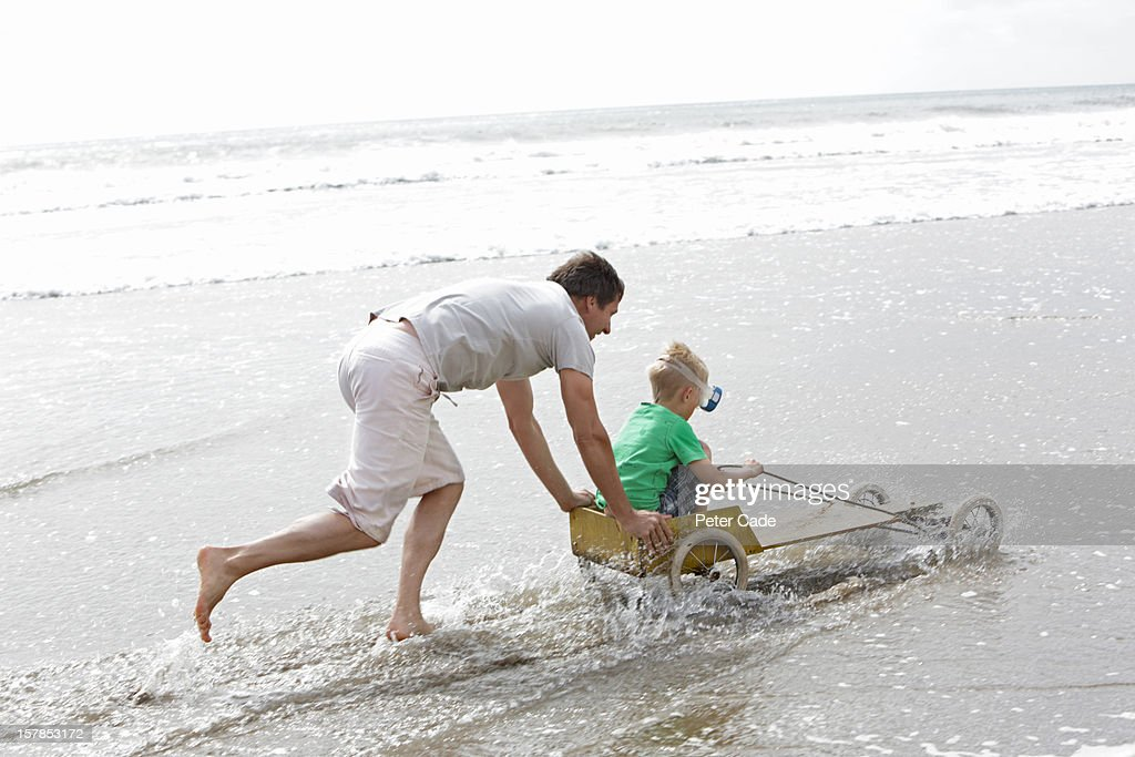 Father pushing son in go-kart on beach : Stock Photo