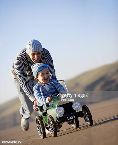 Father pushing son (2-3) in toy car