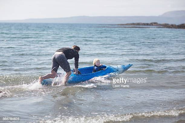 Father pushing son in water in canoe