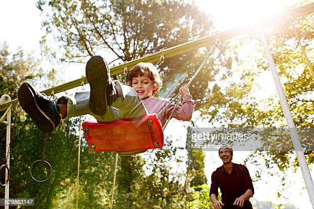 father pushing son on swing in park - swinging stock pictures, royalty-free photos & images