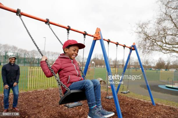 father pushing son (4-5) on swing in park - swinging stock pictures, royalty-free photos & images