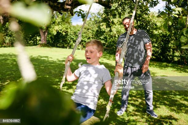 Father pushing son on swing