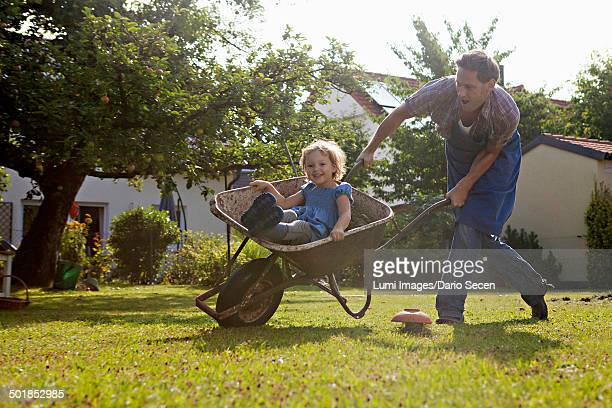 Father pushing wheelbarrow with daughter in the garden, Munich, Bavaria, Germany