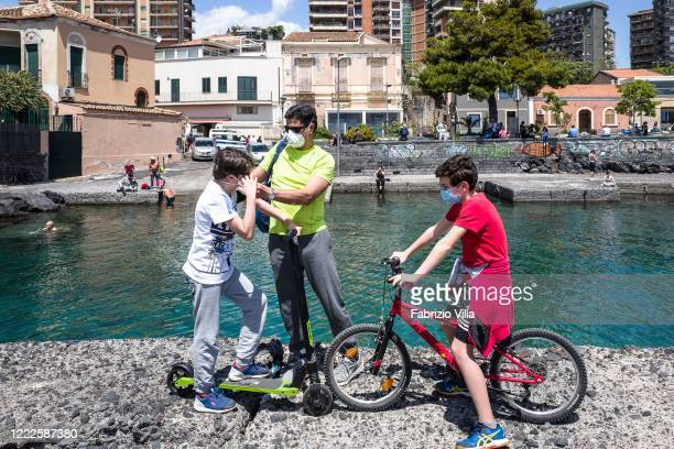 A father puts a protective mask on one of the two children as they stand by the water's edge in the small port of San Giovanni li Cuti in Catania on...