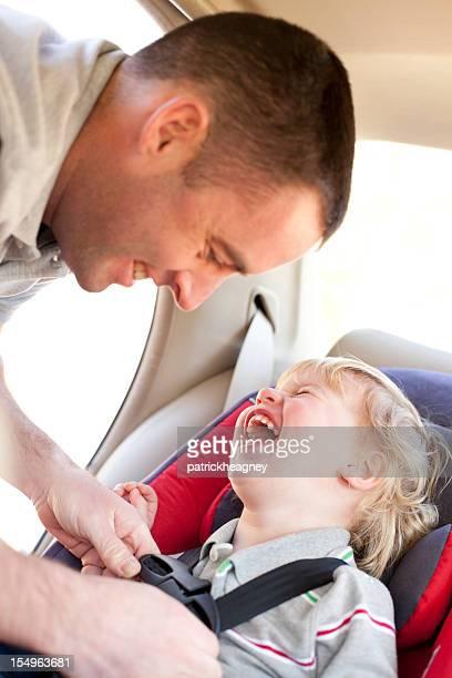 Vater bringt Kind im Auto Sitz