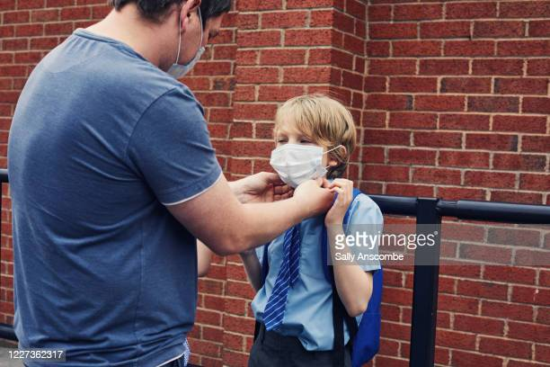 father putting a mask mask on a child - genderblend stock pictures, royalty-free photos & images
