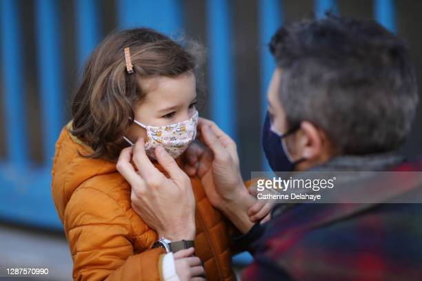 a father putting a protective face mask on his little daughter in front of school - education stock pictures, royalty-free photos & images