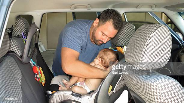 Father putting baby boy in a carseat