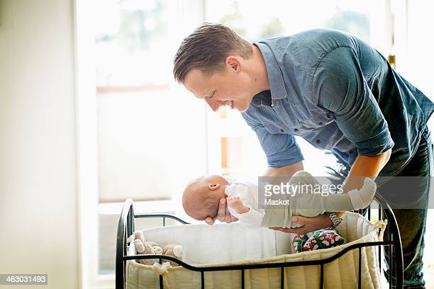 Father putting baby girl in cradle at home