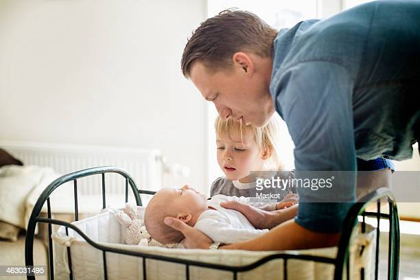 Father putting baby girl in cradle while daughter looking at them