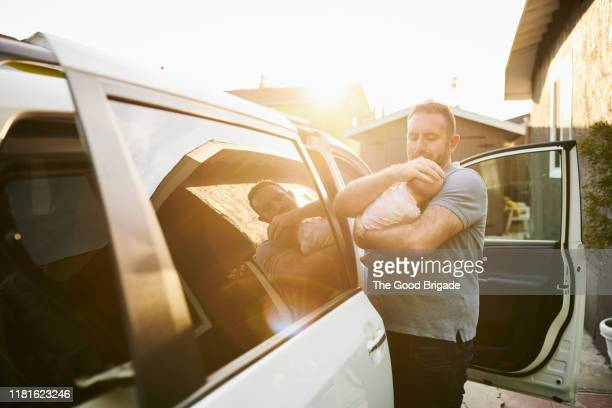 father putting baby girl into car seat - lgbtq  and female domestic life fotografías e imágenes de stock