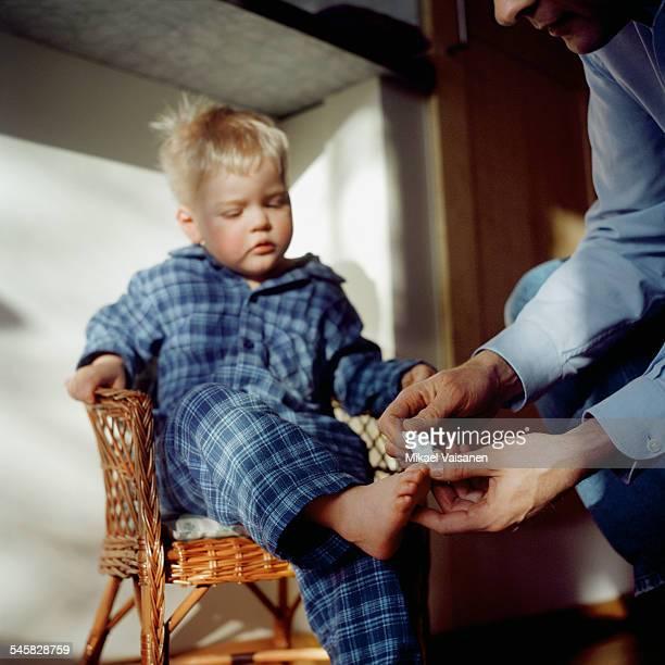father putting bandage on sons foot - plaie photos et images de collection
