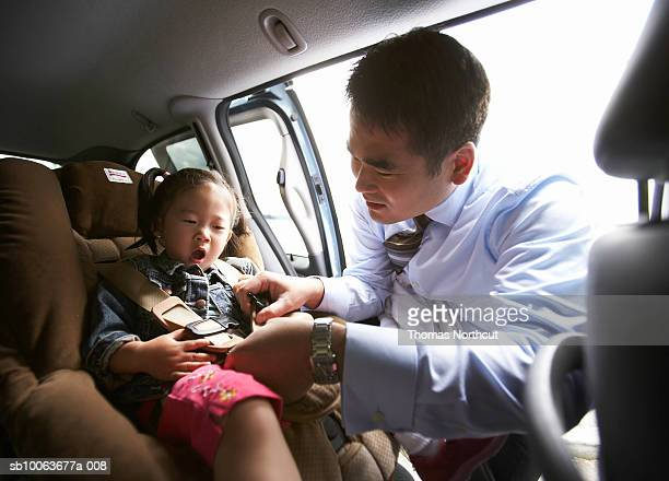 Father putting daughter (1-3) in car safety belt